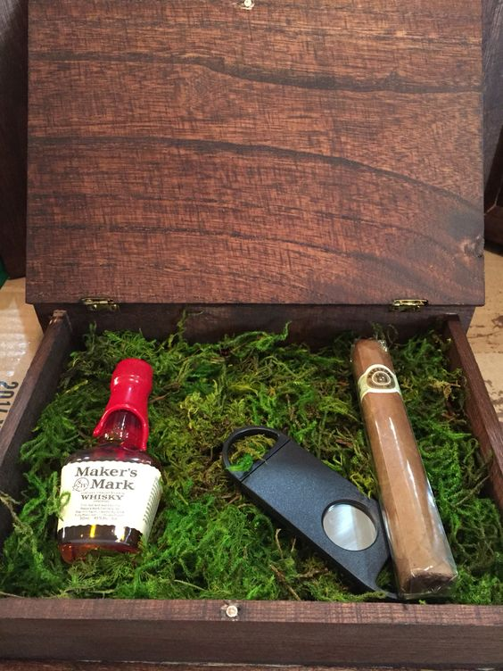 a stained wooden box with moss, a bottle of alcohol, a cigar, a cigar cutter for a woodland-themed wedding