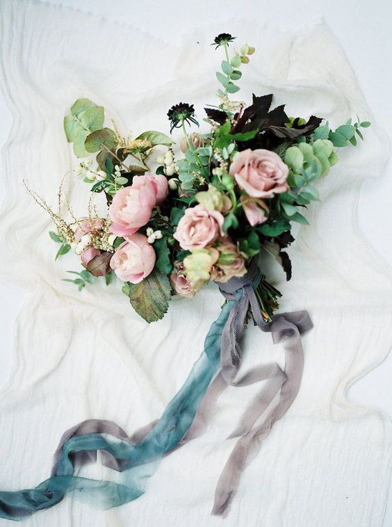 a beautiful bouquet with dusty pink blooms, eucalyptus and dark leaves