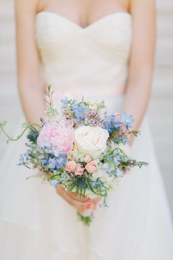 a cute bouquet with blue and pink blooms, a white rose, some thistles and greenery