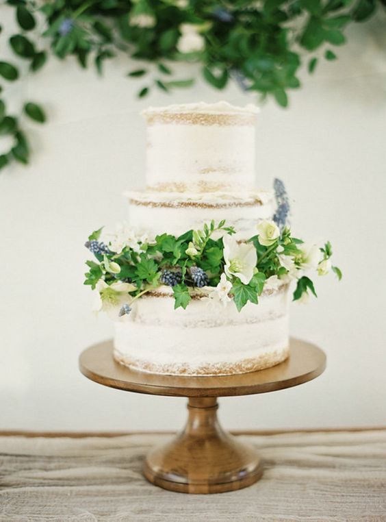 a semi-naked wedding cake with fresh foliage, blooms and blues for a fresh spring look