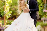 11 a spaghetti strap wedding dress with side cutouts and realistic flower appliques on the skirt
