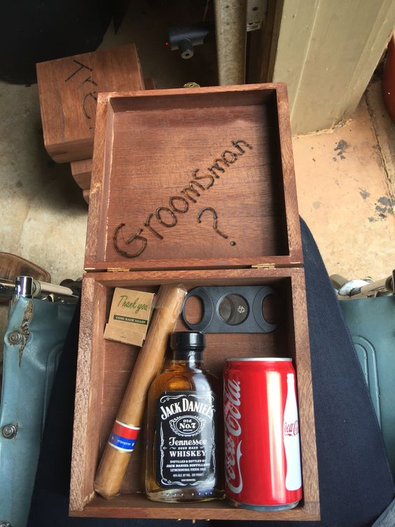 a stained wooden box with a cigar, Jack Daniel's, Coca Cola and a cigar cutter