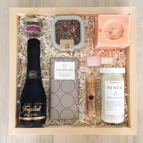 a stylish box with champagne, dried petals and soap for a bath, candies and some Dead Sea salt