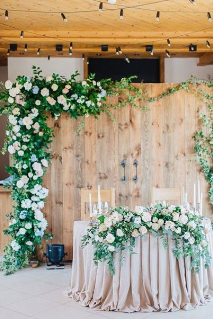 old barn doors decorated with lush blooms and foliage look cute and rustic