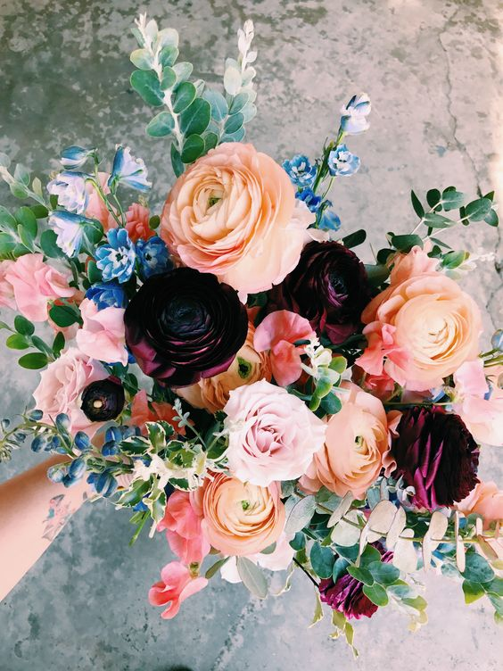 a bold and colorful bouquet in peachy orange, blue and pink is made more moody with deep purple blooms