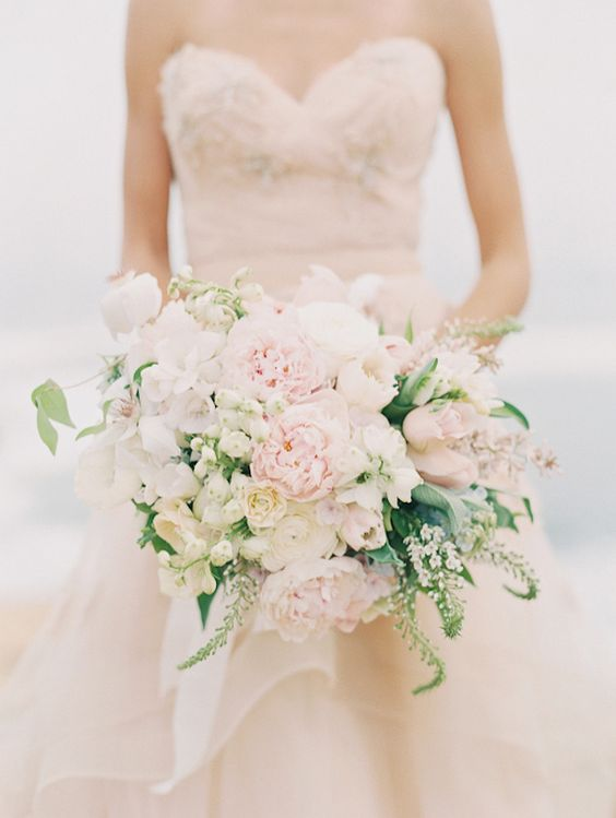 a large blush and cream asymmetrical bridal bouquet with some greenery