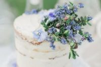 12 a semi-naked wedding cake decorated with blue flowers and foliage looks ethereal