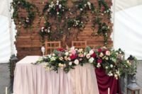 12 a wooden backdrop with greenery and lush blooms and matching ones on the table