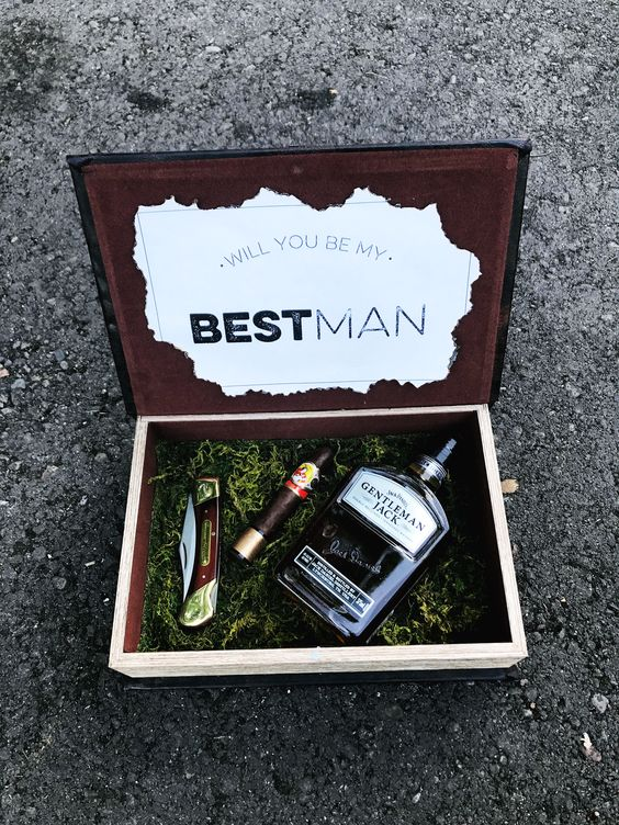 a box with moss, a cigar, a small bottle of alcohol and a knife for a stylish woodland proposal