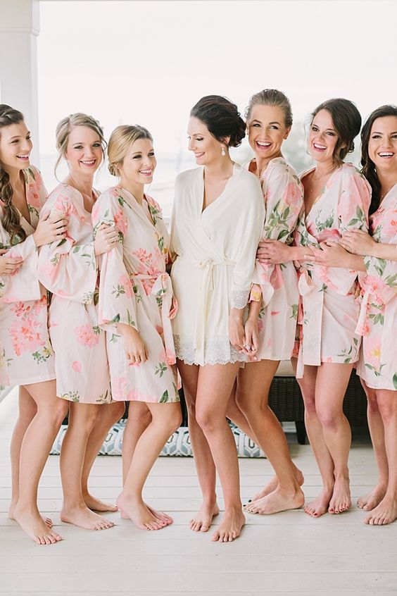 a short bridal robe with lace trim and pink floral print bridesmaids' robes