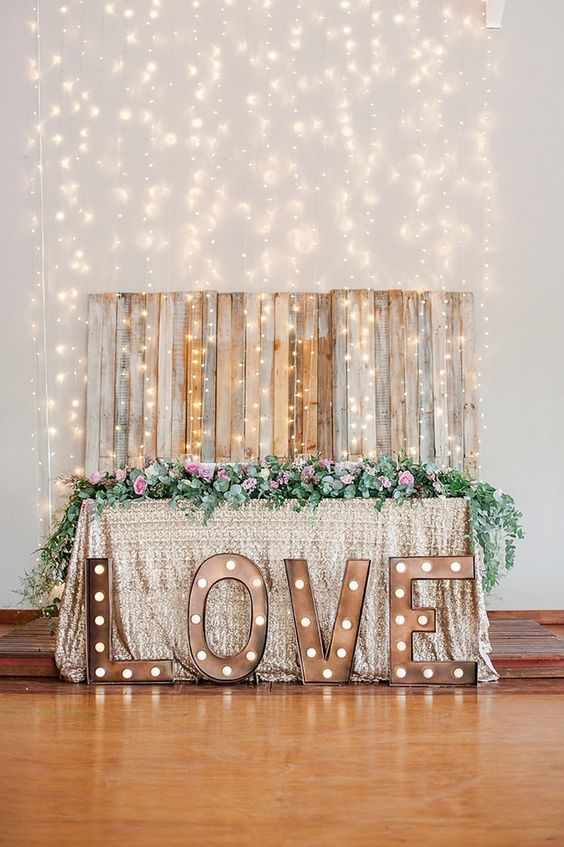 a cool reclaimed wood backdrop with lots of lights hanging from above
