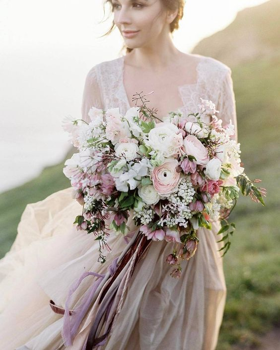 a cute bouquet with white, blush and dusty pink blooms and long ribbons with a texture