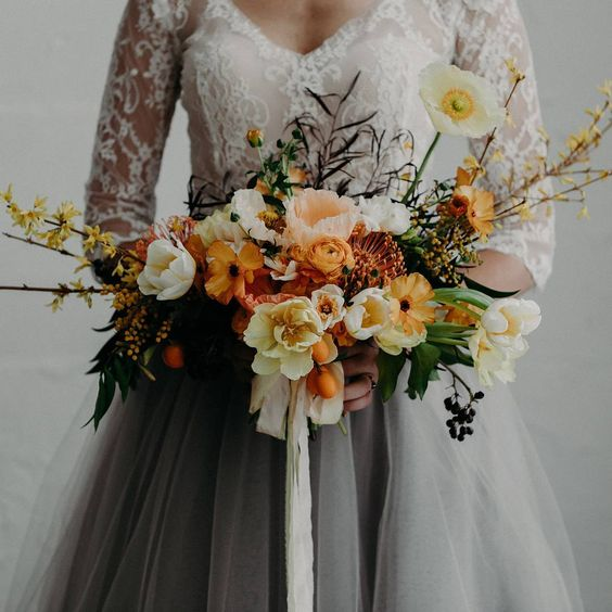 a moody wedding bouquet with orange and yellow splashes and an interesting texture