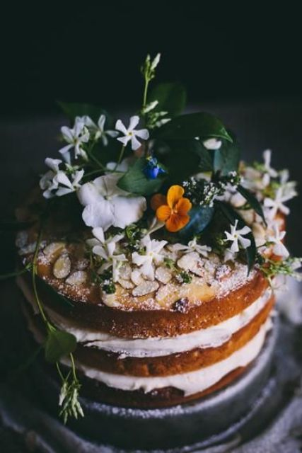 a naked cake topped with almonds, fresh blooms and foliage for a moody spring wedding