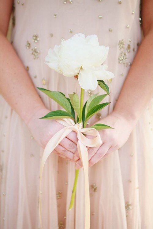 a single stem white bloom will stand out if you are wearing a colored wedding dress