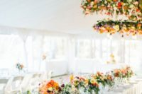 14 bold floral chandeliers over the tables and matching blooms on them