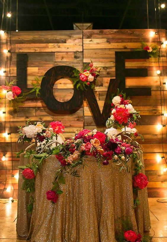a reclaimed wood backdrop with large LOVE letters and bold blooms