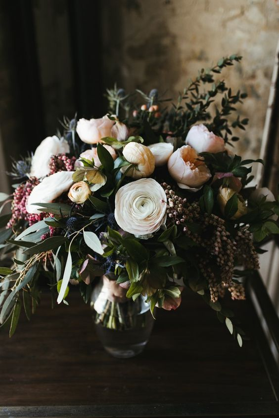 a wedding bouquet of blush and white blooms and blue thistles