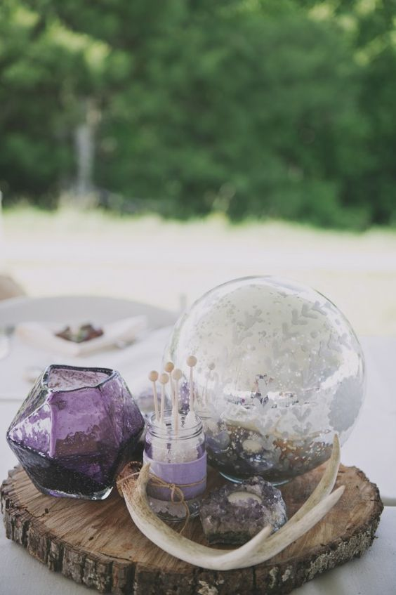 an amethyst candle holder, some geodes and a purple vase for chic table decor