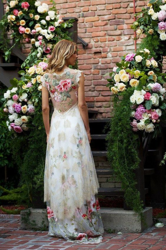 a bold floral wedding dress without sleeves and with an illusion floral back
