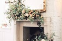 16 a fireplace with greenery and lush blooms to use as a wedding backdrop