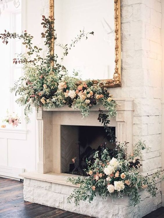 a fireplace with greenery and lush blooms to use as a wedding backdrop
