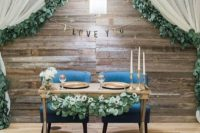 16 a reclaimed wood backdrop with a banner, a lamp and curtains with foliage on the edge