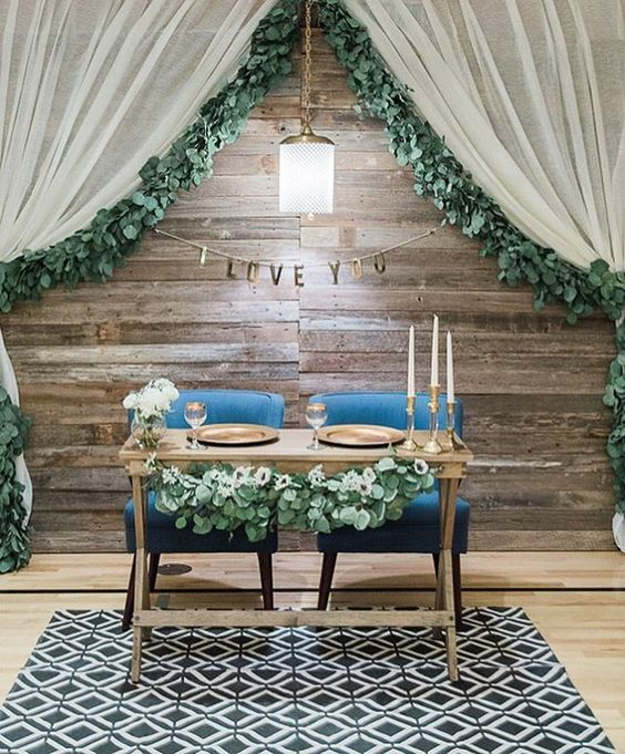 a reclaimed wood backdrop with a banner, a lamp and curtains with foliage on the edge