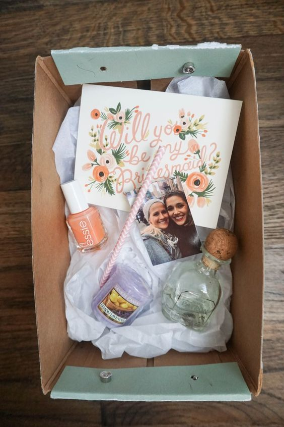 a simple box with a candle, some tequila, bold polish and a photo for a colorful wedding