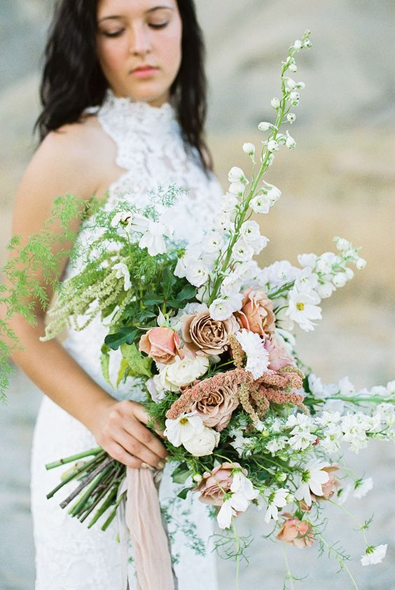 a wedding bouquet with white and dusty pink blooms and greenery looks pastel yet moody