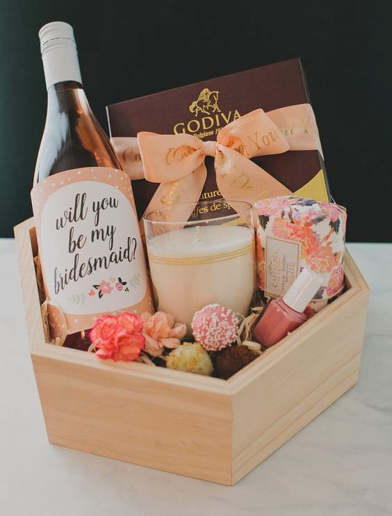 a cute bridesmaid's box with a candle , a soap, some chocolate and pops, a bottle of wine and nail polish
