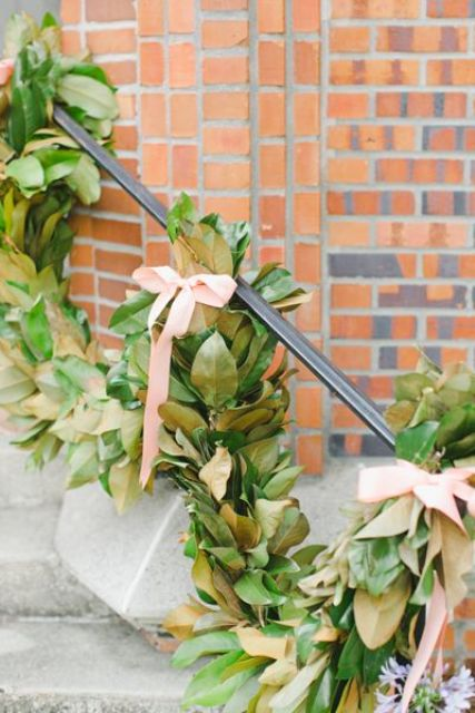 a lush magnolia garland with ribbon bows for staircase decor