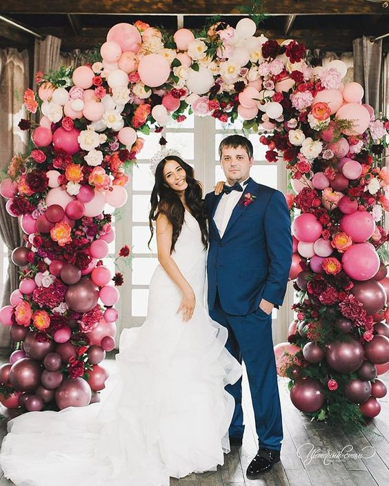 a lush ombre balloon and floral wedding arch is a cool and glam idea