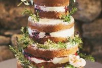 17 a naked wedding cake decorated with blueberries, fresh herbs and some blooms for a rustic feel