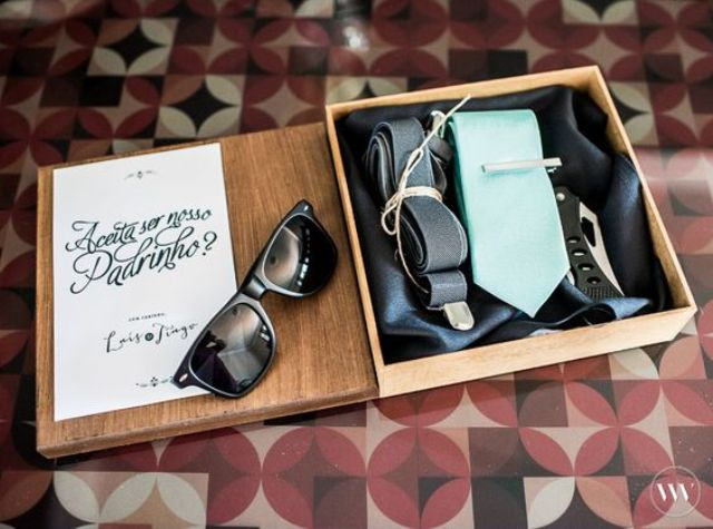 a wooden box with a turquoise tie, suspenders, sunglasses and a knife for a dedstination wedding