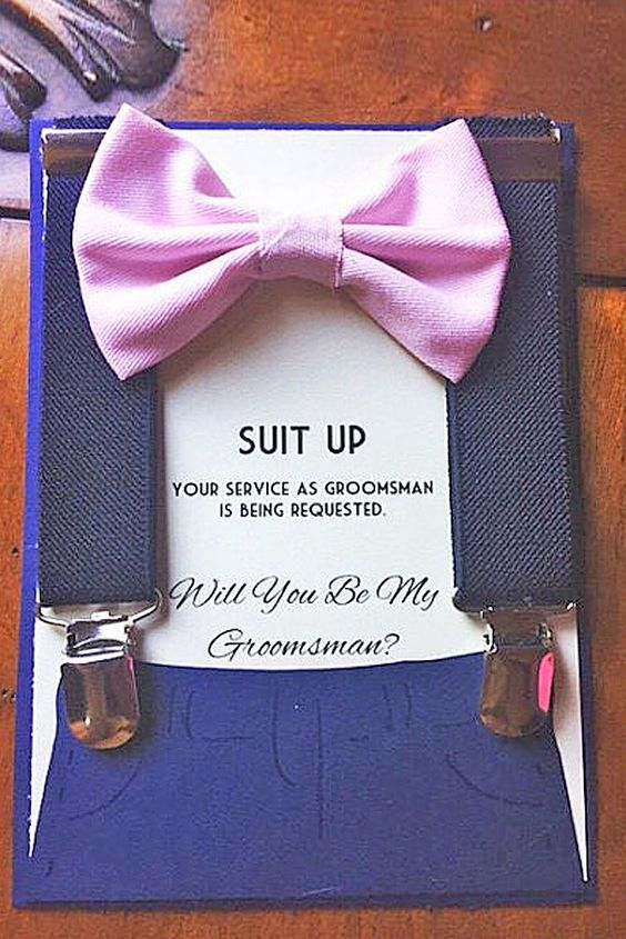 navy suspenders and a pink bow tie for the wedding day on a card