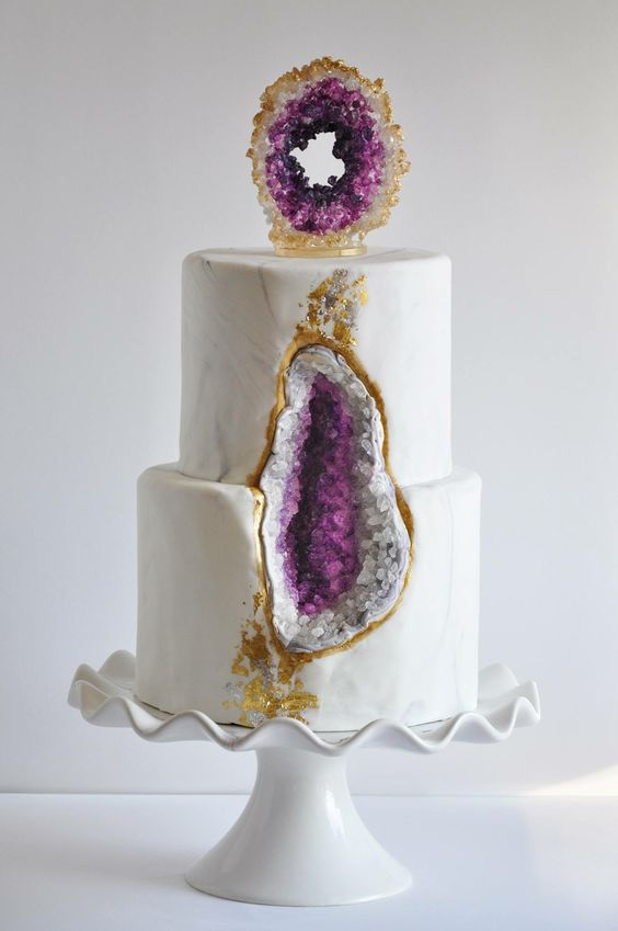 a marbleized wedding cake with amethyst and gold leaf decor and a sugar geode on top