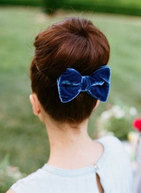 a top knot accessorized with a velvet bow is a classic idea to try
