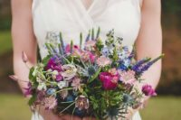 19 a colorful wildflower wedding bouquet with purple, blue and pink blooms and blue thistles