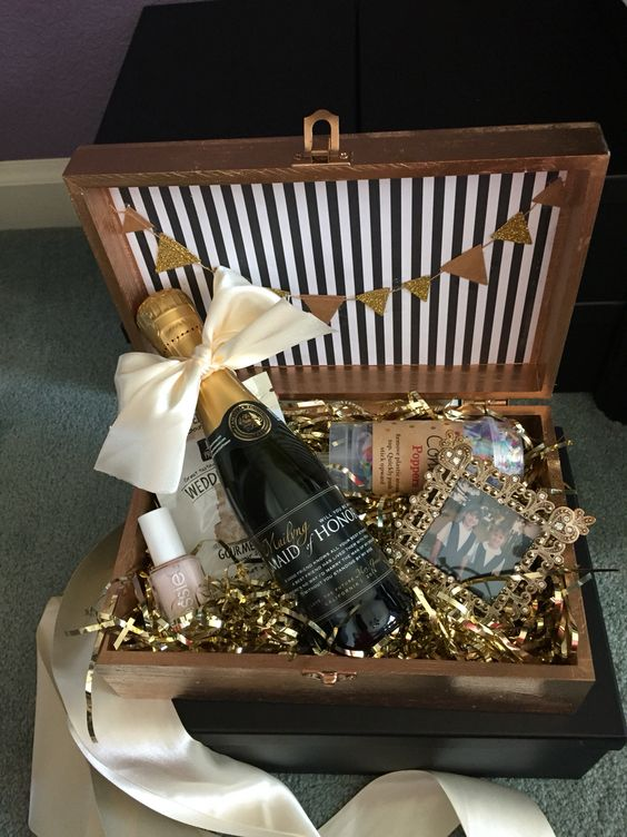 a glam box with champagne, nail polish, cookies, a photo and confetti