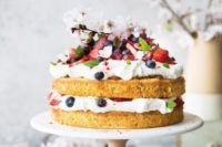 19 a naked wedding cake topped with fresh whipped cream and berries and cherry blossom