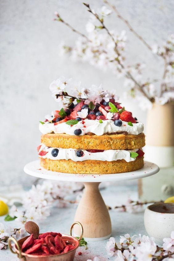 a naked wedding cake topped with fresh whipped cream and berries and cherry blossom