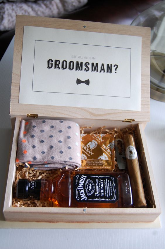 a simple box with a bottle of whiskey, a cigar, socks, a bottle opener and a condom