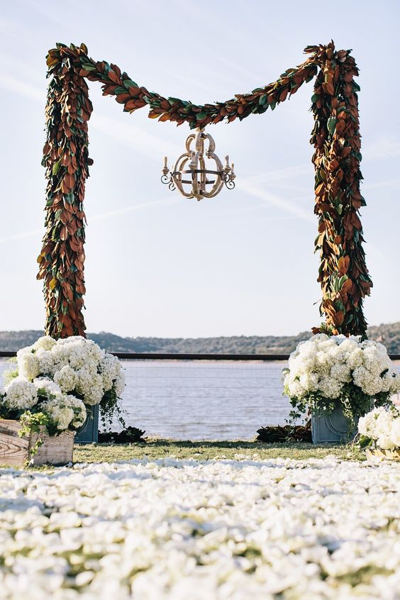 a small chandelier suspended from the center of the alfresco ceremony arch, which is made of magnolia-leaf garlands