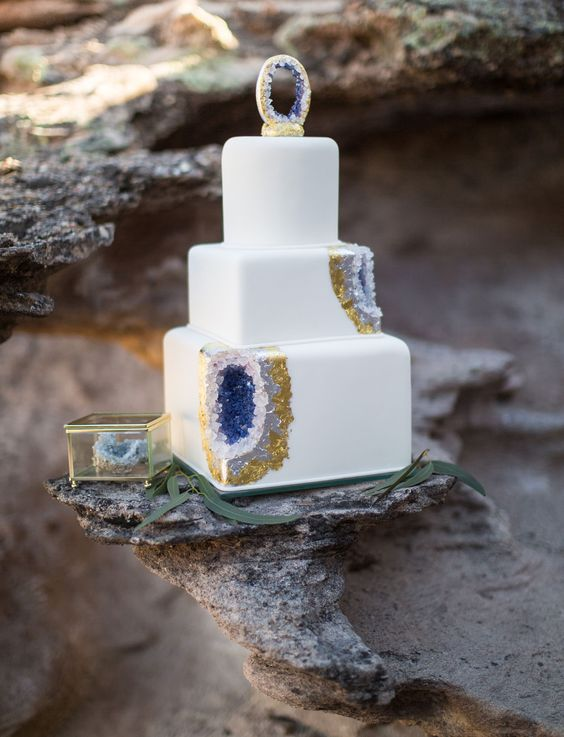 a square wedding cake with amethyst and gold leaf decor and a geode on top looks wow