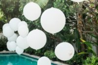 19 a wedding by the pool with balloons over it for a cute touch