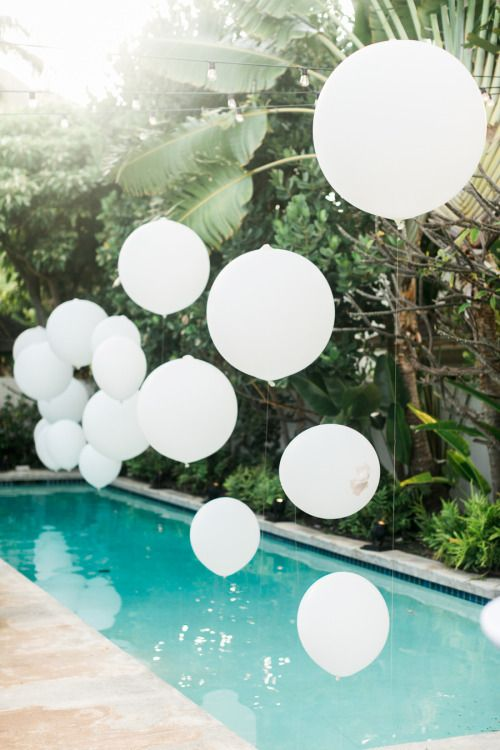 a wedding by the pool with balloons over it for a cute touch