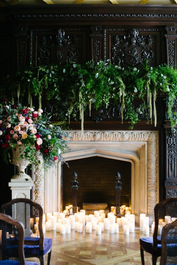 an exquisite fireplace with lush greenery and florals plus lots of candles as a ceremony space