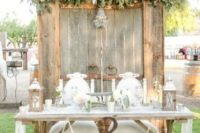 19 an old wooden door backdrop with a glam chandelier and lush blooms and foliage on top