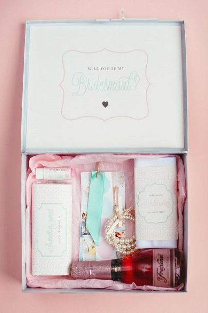 a box with wine, a pearl bracelet, some chocolate and a lip balm